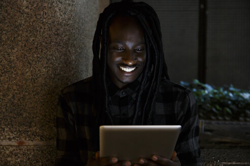 Young black man using digital tablet in the darkness - ABZF001120