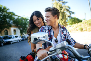 Happy young couple on a motorbike - KIJF000729