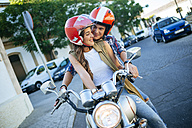 Young couple in love on a motorbike - KIJF000735