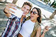 Young couple taking selfie with smartphone - KIJF000744