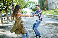 Happy young couple dancing together on pavement - KIJF000747