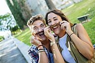 Young couple pulling funny faces - KIJF000750