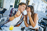 Laughing young couple sitting at sidewalk cafe - KIJF000759