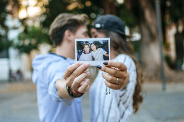 Young couple in love holding photography of themself - KIJF000771