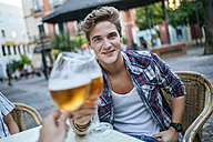 Portrait of young man toasting with glass of beer - KIJF000774