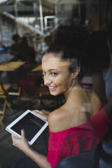 Smiling young woman with tablet looking through window of a coffee shop - MRAF000150