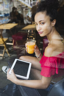 Young woman with glass of orange juice and tablet looking through window of a coffee shop - MRAF000153