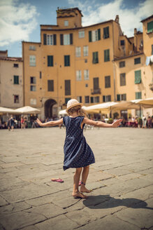 Italy, Lucca, back view of little girl dancing at the Piazza dell'Anfiteatro - OPF000134