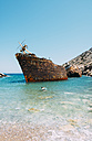 Greece, Cyclades Islands, Amorgos, Man swimming to visit the shipwreck, Olympia - GEMF000994