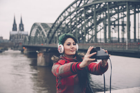 Germany, Cologne, woman taking selfie in front of Hohenzollern Bridge - RTBF000278
