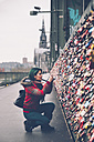 Germany, Cologne, woman taking picture of love locks at Hohenzollern Bridge - RTBF000284