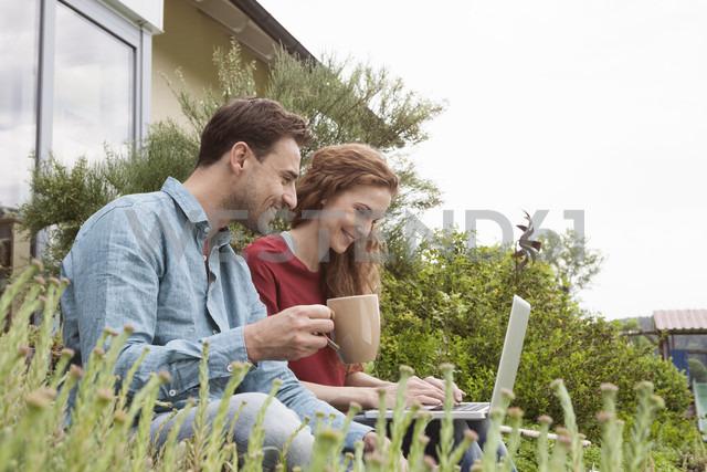 Smiling couple sitting in garden using laptop - RBF005092