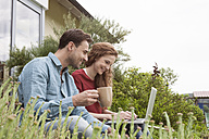 Smiling couple sitting in garden using laptop - RBF005092