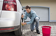 Man cleaning car on driveway of a house - RBF005095