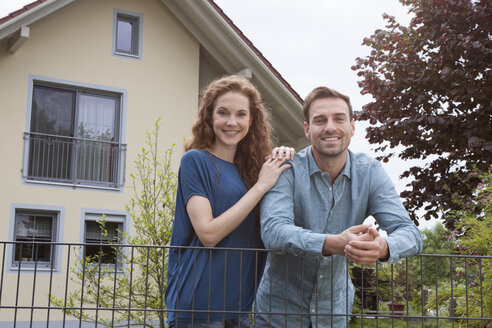 Portrait of smiling couple at garden fence in front of house - RBF005098