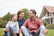 Smiling family sitting in garden - RBF005104