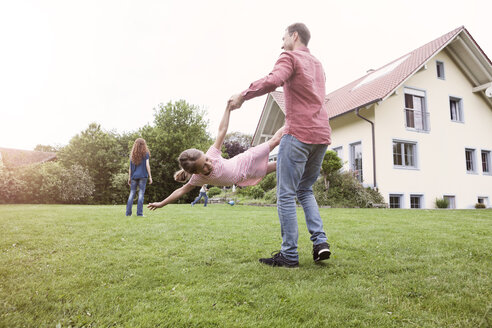 Father playing with daughter in garden - RBF005110