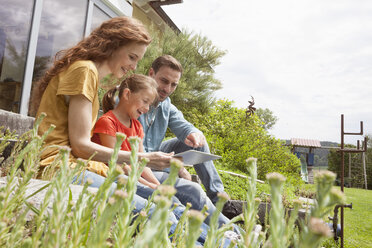 Happy family sitting in garden using tablet - RBF005116