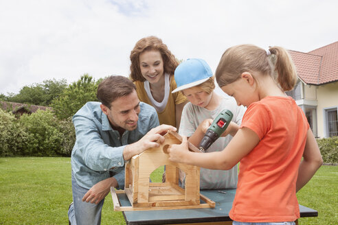 Family building up a birdhouse together - RBF005119