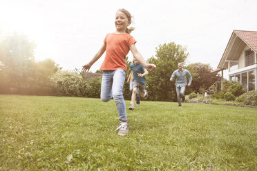 Carefree family running in garden - RBF005122