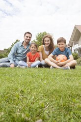 Portrait of smiling family sitting in garden - RBF005125