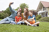 Smiling family sitting in garden taking a selfie - RBF005128