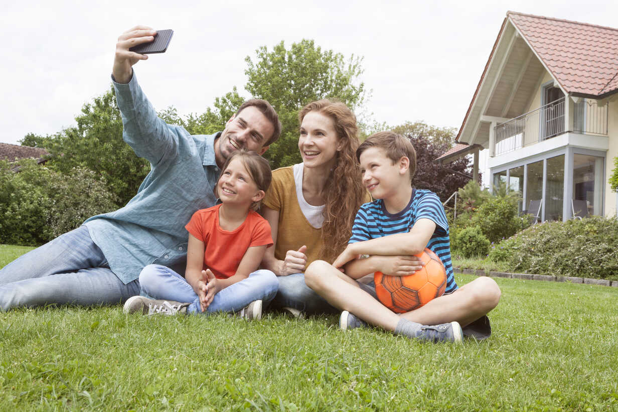 Smiling family sitting in garden taking a selfie - RBF005128 - Rainer Berg/Westend61