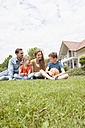Smiling family sitting in garden with football - RBF005131