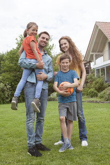 Portrait of smiling family standing in garden - RBF005134