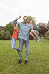 Portrait of happy father carrying his two children in garden - RBF005137