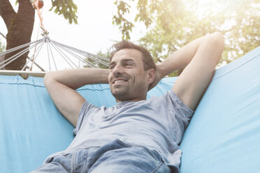 Smiling man relaxing in hammock - RBF005143