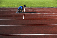 Runner on tartan track in starting position - UUF008290