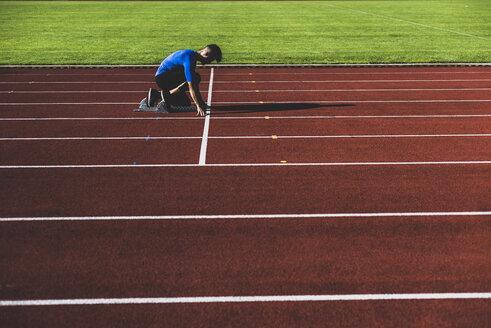 Runner on tartan track in starting position - UUF008290