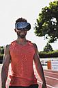 Smiling athlete on tartan track wearing virtual reality glasses - UUF008314
