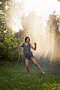 Girl singing and dancing while splashing water with garden hose - LVF005239