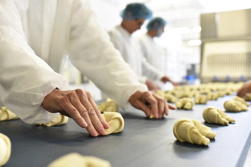 Workers at production line in a baking factory with croissants - LYF000535