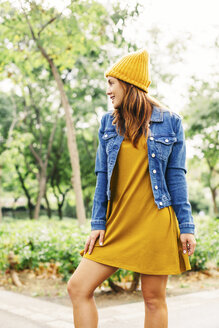 Smiling young woman wearing yellow cap and dress in autumn - EBSF001675