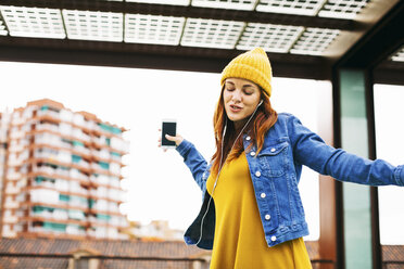 Young woman with yellow cap dancing while listening music with earphones - EBSF001678