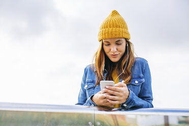 Smiling young woman wearing yellow cap looking at cell phone - EBSF001684