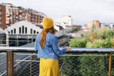 Back view of young woman wearing  yellow cap looking at view - EBSF001693