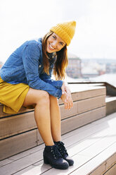 Portrait of smiling young woman wearing yellow cap sitting on steps - EBSF001696