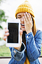 Portrait of laughing young woman showing smartphone with her own picture - EBSF001699