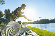 Athlete jumping over bench at the riverside - DIGF001065