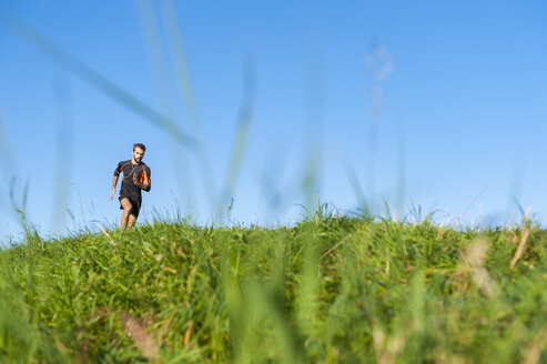 Man running on meadow under blue sky - DIGF001074