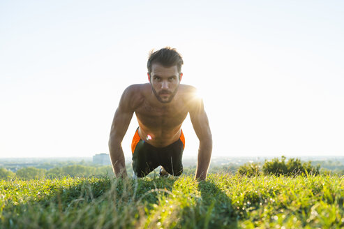 Man doing pushups on a meadow - DIGF001083