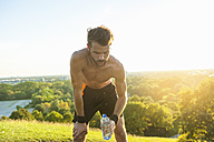 Barechested athlete holding water bottle at sunset - DIGF001104