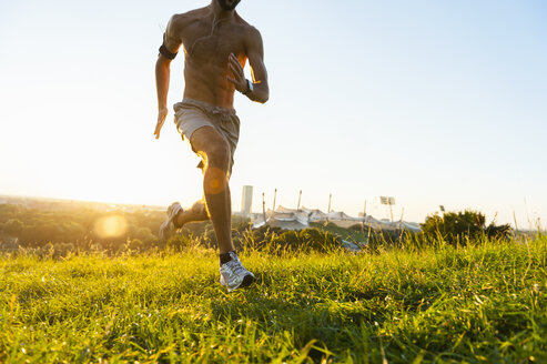 Barechested man running on meadow in park at sunset - DIGF001110