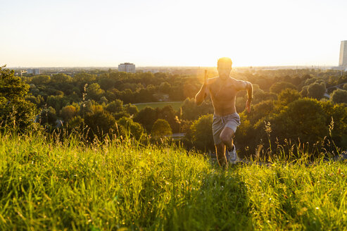 Barechested man running on meadow in park at sunset - DIGF001113