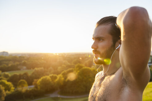Barechested athlete with earbuds at sunset - DIGF001116