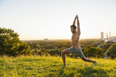 Barechested athlete stretching on meadow at sunset - DIGF001122